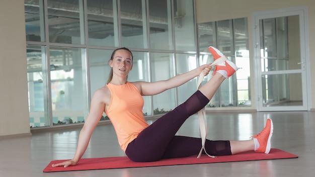 Jolie fille en vêtements de sport faisant de l'échauffement sur le tapis dans la salle de sport avec du ruban adhésif et regardant la caméra