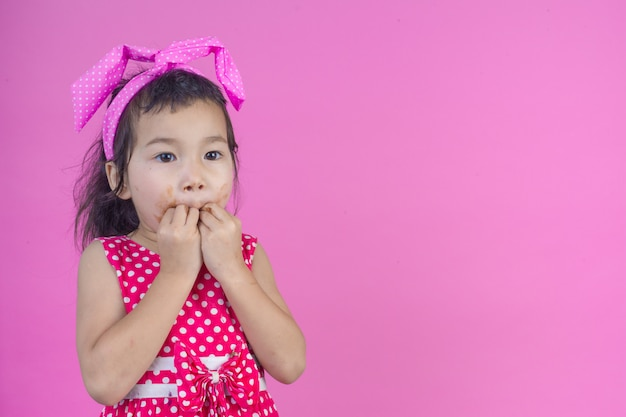 Une jolie fille vêtue d'une chemise rayée rouge mangeant un chocolat avec une bouche sale sur le rose.