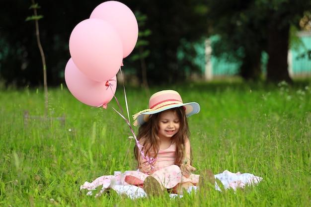 Jolie fille vêtue d'une robe rose avec un chapeau est assise sur l'herbe dans le parc. photo de haute qualité