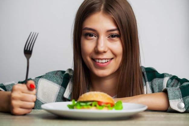 Jolie fille veut manger un hamburger nuisible