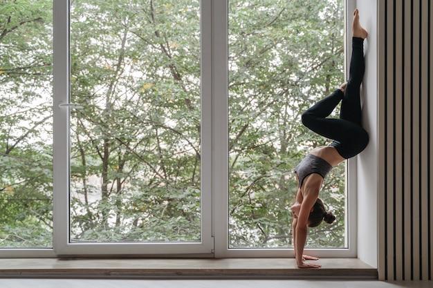 Jolie fille de yoga debout sur les mains contre le mur à la lumière du jour près de la grande fenêtre