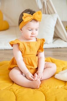 Une jolie fillette d'un an en vêtements jaunes est assise par terre et regarde vers le bas. photo en studio pour l'anniversaire d'un enfant.