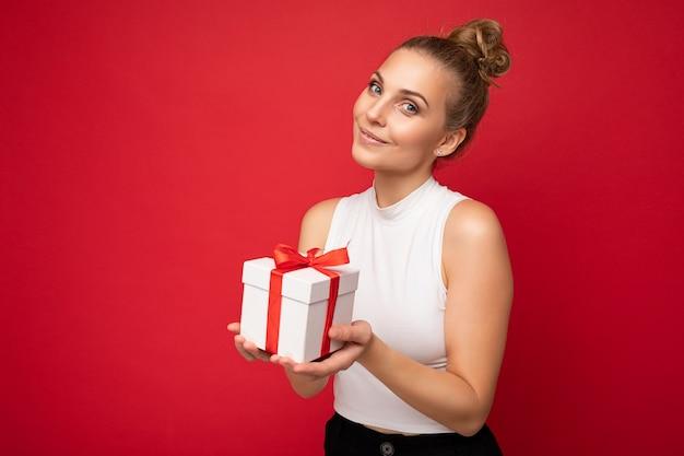 Jolie heureuse jeune personne de sexe féminin blonde isolée sur un mur rouge portant un haut blanc