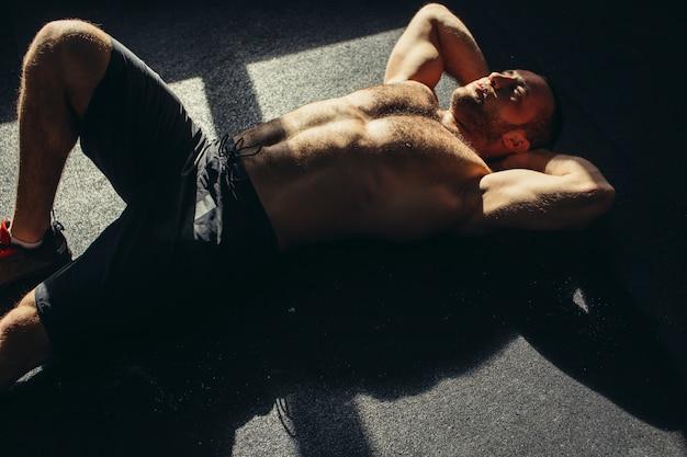 Jolie homme fatigué après l'haltérophilie au gymnase