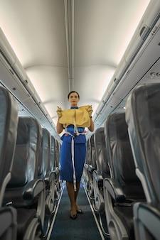 Jolie hôtesse de l'air confiante démontrant un gilet de sauvetage et donnant des instructions de sécurité avant le décollage