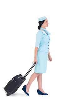 Jolie hôtesse de l'air à pied avec valise