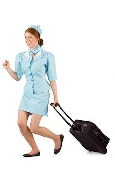 Jolie hôtesse de l'air tirant la valise