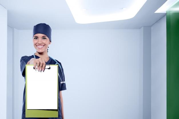 Jolie infirmière asiatique avec stéthoscope montrant le presse-papier vide pour la surface