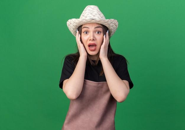 Une jolie jardinière caucasienne anxieuse portant un chapeau de jardinage met les mains sur le visage isolé sur un mur vert avec espace pour copie