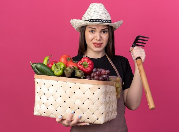 Jolie jardinière caucasienne anxieuse portant un chapeau de jardinage tenant un panier de légumes et un râteau