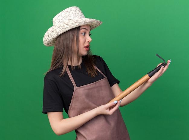 Jolie jardinière caucasienne anxieuse portant un chapeau de jardinage tenant et regardant un râteau