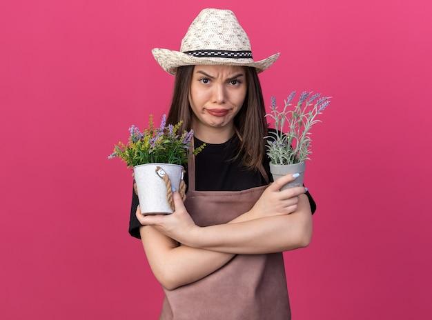 Une jolie jardinière caucasienne en colère portant un chapeau de jardinage se tient avec les bras croisés tenant des pots de fleurs