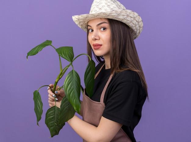 Une jolie jardinière caucasienne confiante portant un chapeau de jardinage se tient sur le côté tenant une branche de plante isolée sur un mur violet avec espace pour copie