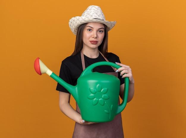 Jolie jardinière caucasienne confiante portant un chapeau de jardinage tenant un arrosoir isolé sur un mur orange avec espace pour copie