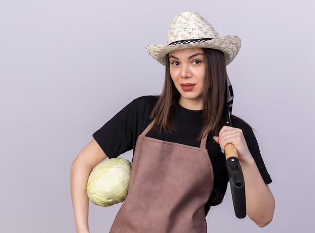 Jolie jardinière caucasienne confiante portant un chapeau de jardinage tenant du chou et une pelle sur l'épaule