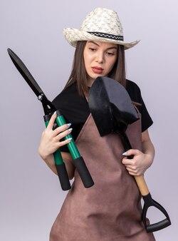 Jolie jardinière caucasienne confiante portant un chapeau de jardinage tenant une pelle et regardant des ciseaux de jardinage
