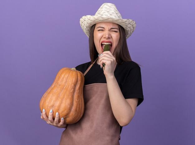 Une jolie jardinière caucasienne mécontente portant un chapeau de jardinage tenant une citrouille et un concombre mordant isolé sur un mur violet avec espace pour copie