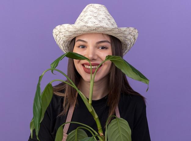 Une jolie jardinière caucasienne souriante portant un chapeau de jardinage tient une branche de plante