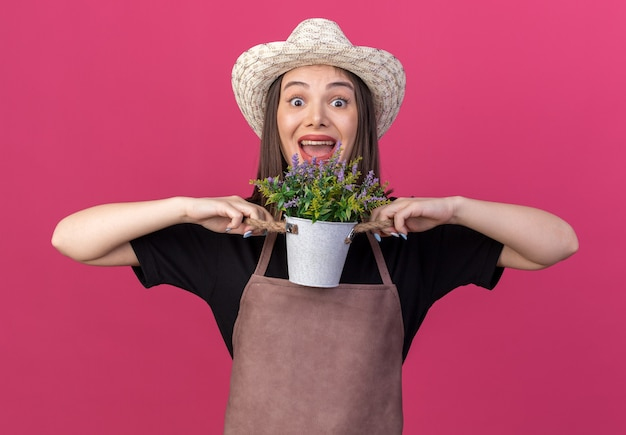 Jolie jardinière caucasienne surprise portant un chapeau de jardinage tenant des fleurs dans un pot de fleurs isolé sur un mur rose avec espace pour copie