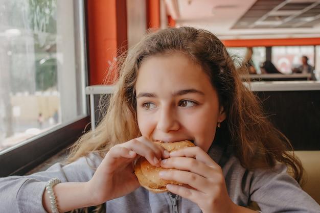 Jolie jeune adolescente avec un appétit en train de manger un hamburger dans un café