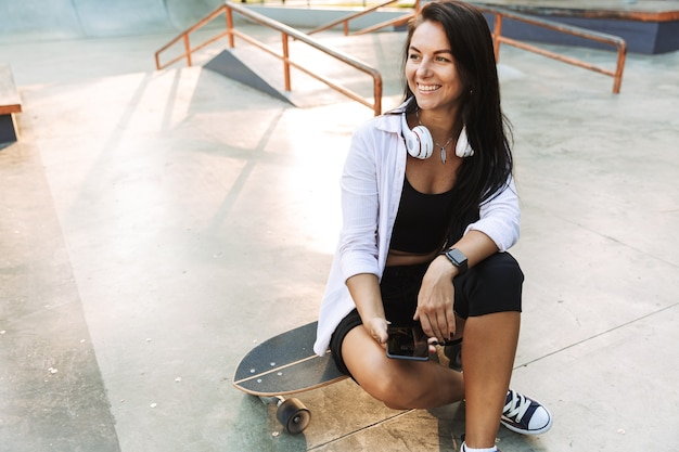 Jolie jeune adolescente assise au skatepark avec un longboard, tenant un téléphone portable