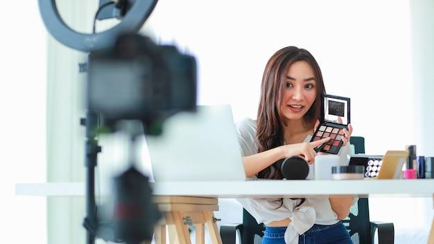 Jolie et jeune blogueuse ou vlogger diffusant ou enregistrant une vidéo pour le blog beauté beauté et cosmétiques. l'influenceur vit la vidéo sur le réseau social. concept de blog, vidéoblog, maquillage.