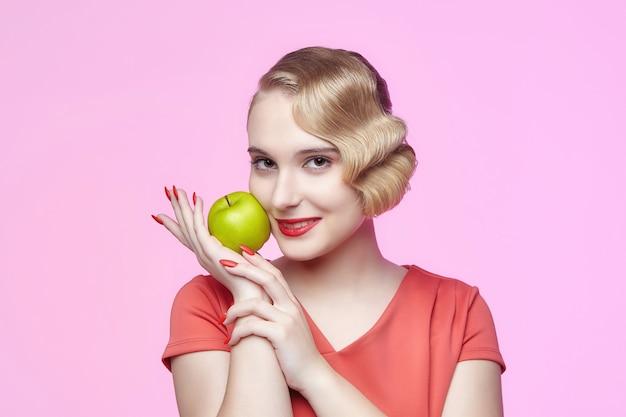 Jolie jeune blonde avec une coiffure rétro tient une pomme verte près de son visage