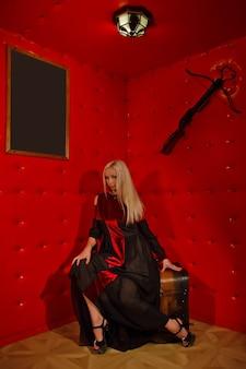 Jolie jeune blonde sexy en robe gothique à l'intérieur de la salle de torture rouge médiévale est assise sur la poitrine contre le mur texturé. image de la reine d'horreur d'halloween. copiez l'espace pour le texte ou le logo