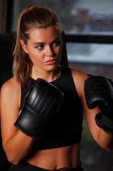 Jolie jeune boxeuse debout dans le coin ring de boxe levant les mains dans une ancienne salle de sport, sa main dans les gants. femme en formation de boîte. concept de mode de vie sain, de sport et d'exercice en salle de sport. espace de copie
