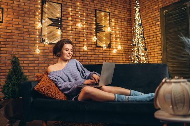 Jolie jeune brune à la maison sur le canapé à l'aide d'un ordinateur portable