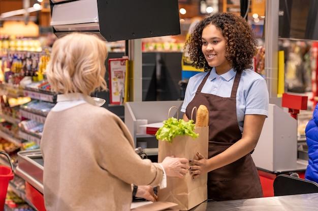 Jolie jeune caissière donnant un sac en papier avec du pain et des produits d'épicerie frais tout en se tenant debout par une caisse enregistreuse dans un supermarché