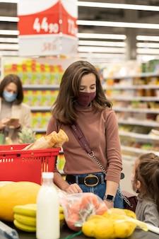 Jolie jeune caissière donnant un sac en papier femme mature avec du pain et des produits d'épicerie frais tout en restant debout près de la caisse enregistreuse dans un supermarché