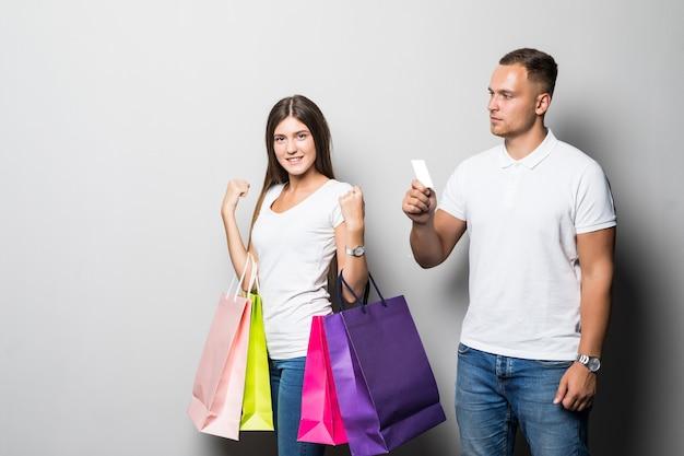 Jolie jeune couple étudiant ensoleillé souriant tenant beaucoup de sacs de couleur isolé sur fond blanc