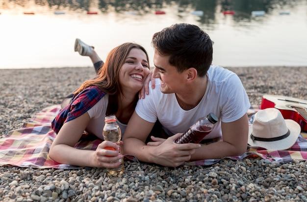 Jolie jeune couple s'amusant au bord du lac