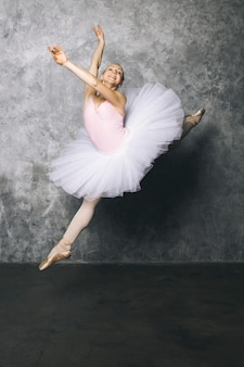 Jolie jeune danseuse de ballerine dansant le ballet classique contre un mur rustique