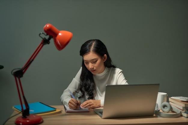 Jolie jeune étudiante assise au bureau et faisant ses devoirs, elle se connecte à internet avec un ordinateur portable