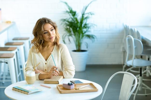 Jolie jeune étudiante blonde avec un crayon sur un livre assis par table dans un café, penser aux devoirs et prendre un café