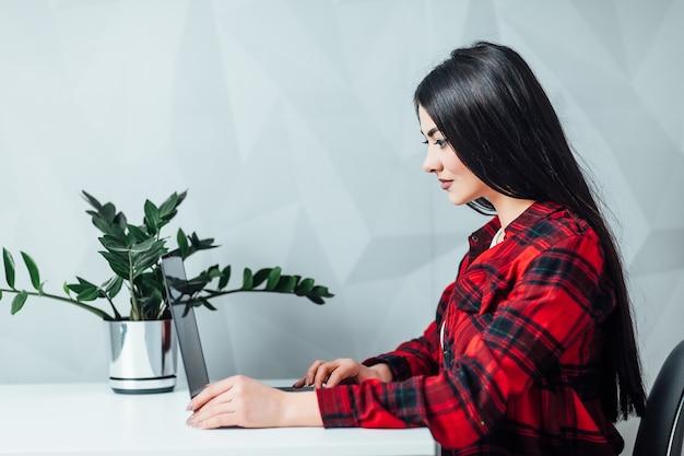 Jolie jeune étudiante travaille avec un ordinateur portable