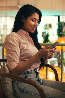 Jolie Jeune étudiante Vêtue D'un Chemisier Rose Et D'un Jean Souriant Assise Seule Et Regardant L'écran De Son Smartphone Moderne Photo Premium