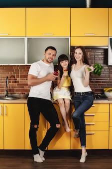 Jolie jeune famille, maman, papa et petite fille posant dans une cuisine à la mode tenant des verts