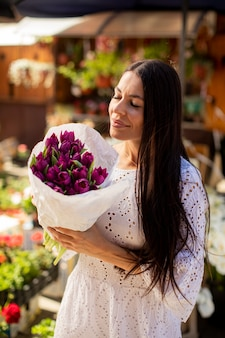 Jolie jeune femme achetant des fleurs au marché aux fleurs