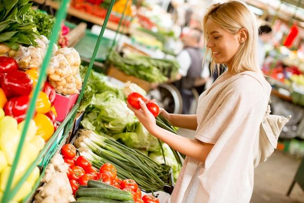 Jolie jeune femme achète des légumes au marché