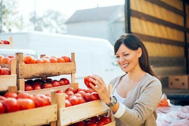 Jolie jeune femme achète des légumes sur le marché.