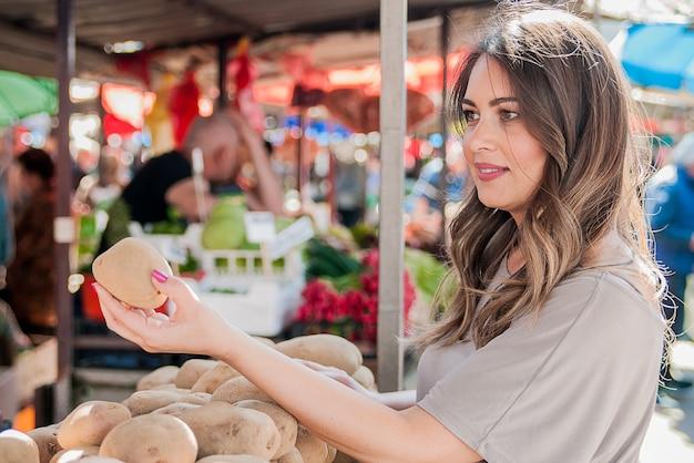 Une jolie jeune femme achète des pommes de terre sur le marché. shopping, vente, consommation et concept de personnes. femme achetrice choisissant des pommes de terre fraîches à partir d'un bac au marché des fermiers