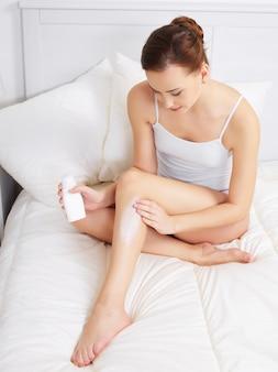 Jolie jeune femme adulte appliquant la crème pour la peau sur les jambes