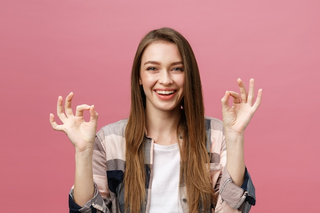 Jolie jeune femme adulte montrant le signe ok