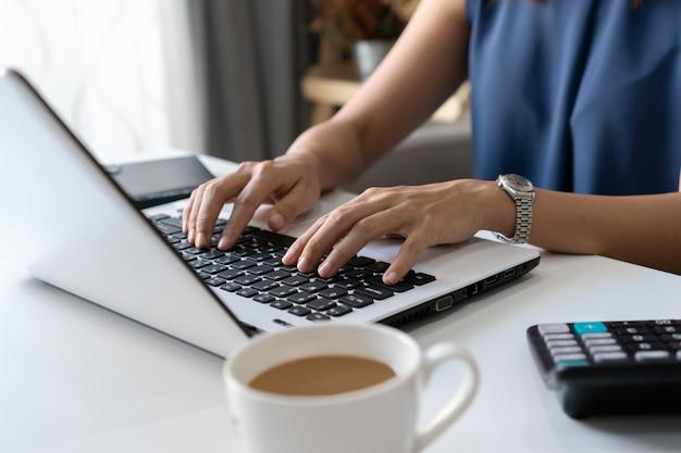 Jolie jeune femme d'affaires asiatique travaillant avec un ordinateur portable dans le salon.