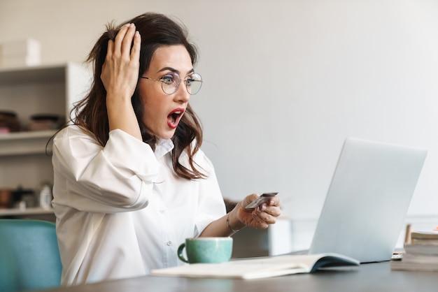 Jolie jeune femme d'affaires brune choquée et bouleversée assise à la table du café avec un ordinateur portable à l'intérieur, faisant des achats en ligne avec une carte de crédit
