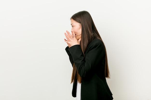 Une jolie jeune femme d'affaires chinoise crie fort, garde les yeux ouverts et les mains tendues.