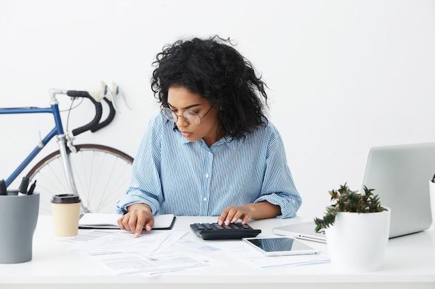 Jolie jeune femme d'affaires confiante avec une coiffure frisée à l'aide de la calculatrice
